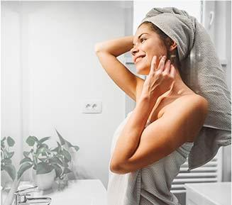 Woman in bathroom with hair wrapped in towel